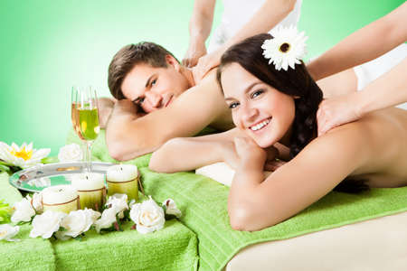 Portrait of smiling young couple receiving shoulder massage at beauty spa photo