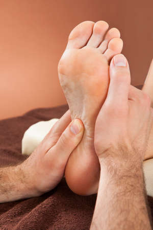 Closeup of male therapist giving foot massage to female customer at beauty spa photo