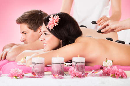 Portrait of smiling young couple receiving massage with herbal compress stamps on back at spa photo