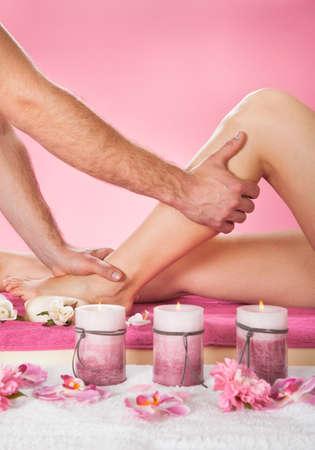 Cropped image of male therapist massaging female customers leg at beauty spa photo