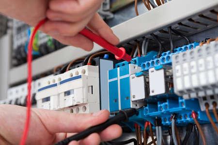 Zbliżenie męskiej elektryk bada fusebox z sondy multimetru