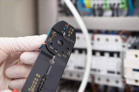 Cropped image of male electrical engineer cutting cable with fusebox in background photo