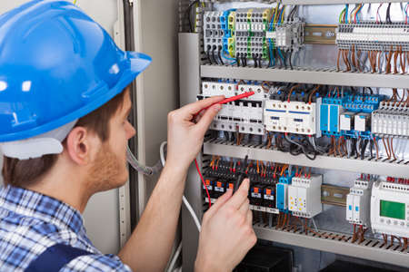maintenance engineer: Side view of male technician examining fusebox with multimeter probe