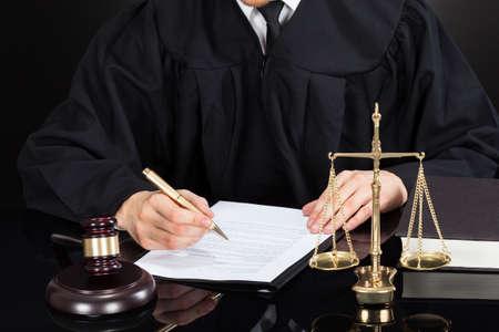 Buik van mannelijke rechter schriftelijk op papier op het bureau tegen zwarte achtergrond