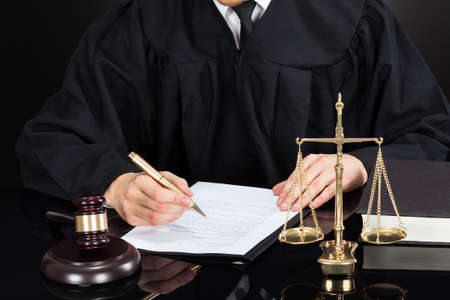 judge hammer: Midsection of male judge writing on paper at desk against black background