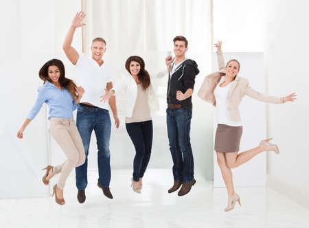Full length portrait of confident businesspeople jumping with arms raised in office photo