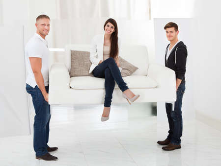 Full length portrait of movers carrying sofa with happy client woman sitting photo