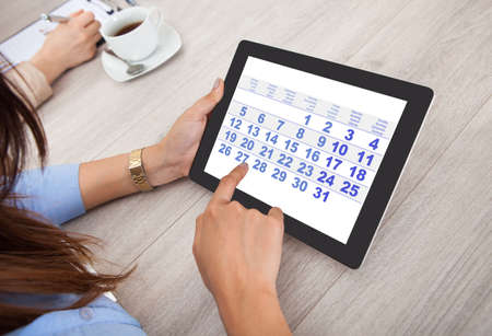 Cropped image of businesswoman using digital tablet at desk in office Stock Photo
