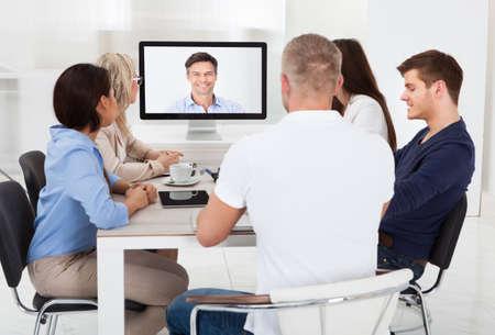 Personas del asunto que asistía a una conferencia de vídeo en el escritorio en la oficina Foto de archivo - 28755785