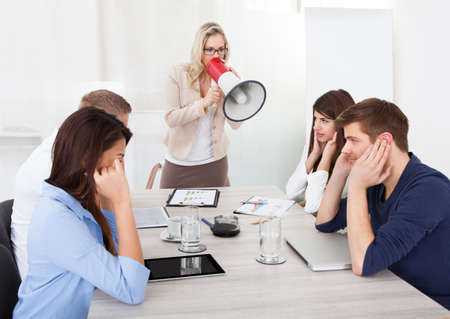 Angry businesswoman shouting through megaphone on colleagues in meeting at office photo