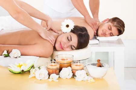 Portrait of smiling young couple receiving massage at spa photo