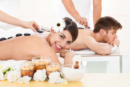 four hands: Young couple receiving Lastone therapy at beauty spa