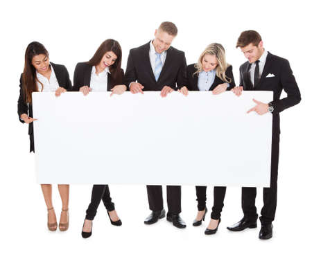Full length portrait of confident businesspeople holding blank banner against white background Stock Photo
