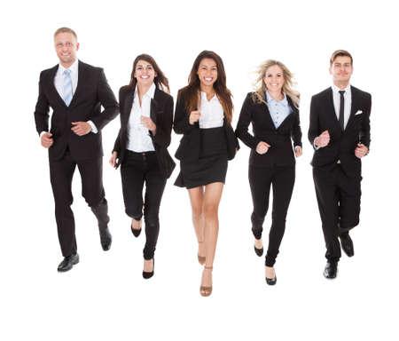 Full length portrait of welldressed businesspeople running against white background Imagens