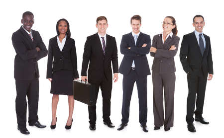 Full length portrait of confident business team standing against white background