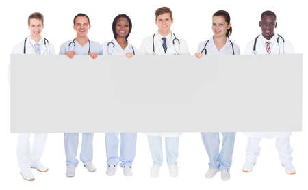 Full length portrait of confident doctors holding blank billboard over white background photo