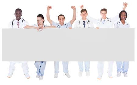 Full length portrait of confident doctors holding blank billboard over white background photo