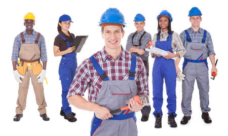 Portrait of confident male engineer holding tool with team against white background photo