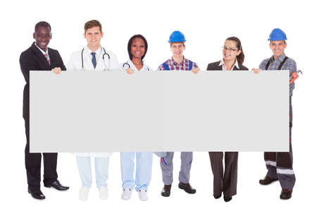 various occupations: Full length portrait of smiling people with various occupations holding blank billboard over white background Stock Photo