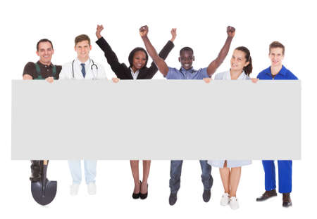 Full length portrait of successful people with different occupations holding blank billboard against white background photo