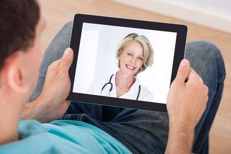 남자는 집에서 디지털 태블릿에 여성 의사와 비디오 채팅을하는 데