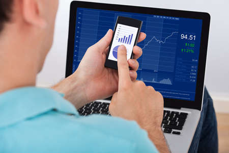 stock image: Cropped image of man analyzing stock market using smartphone and laptop at home