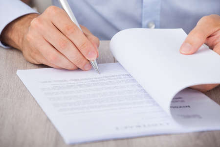 financial audit: Cropped image of businessman signing contract at desk