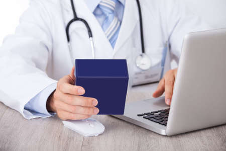 Midsection of doctor holding medicine box while using laptop in clinic photo
