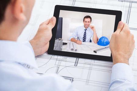 Image recadrée d'hommes conférence architecte de vidéo avec un collègue par tablette numérique dans le bureau