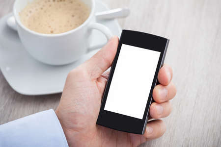 Closeup of businessmans hand holding cellphone with blank screen on desk photo