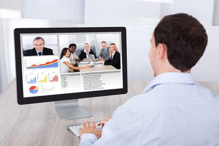 オフィスの机でデスクトップ PC 上のビジネスマンの同僚とのビデオ会議の背面図