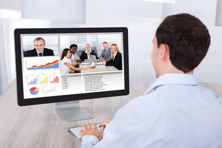 Webinar: Rear view of businessman video conferencing with colleagues on desktop PC at office desk
