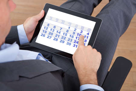 Overhead view of businessman using calendar on digital tablet in office photo