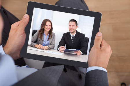 High angle view of businessman video conferencing with colleagues on digital tablet in office photo