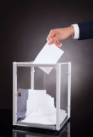 Cropped image of businessman inserting ballot in box on desk against black background photo