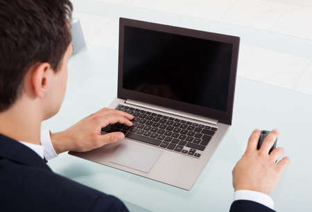 Cropped image of young businessman using laptop at desk in office photo