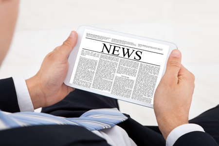 High angle view of businessman reading news on digital tablet in office photo