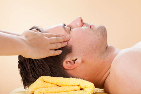 male massage: Side view of young man receiving forehead massage in spa Stock Photo