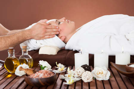 Side view of relaxed young woman receiving head massage at beauty spa photo