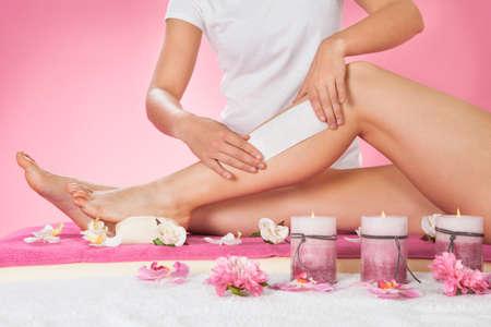 depilacion con cera: Sección media de la pierna femenina del cliente terapeuta encerado en el spa de belleza