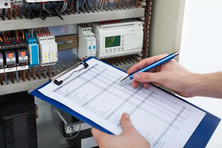 Bebouwd beeld van mannelijke elektricien bedrijf klembord terwijl het onderzoeken zekeringkast