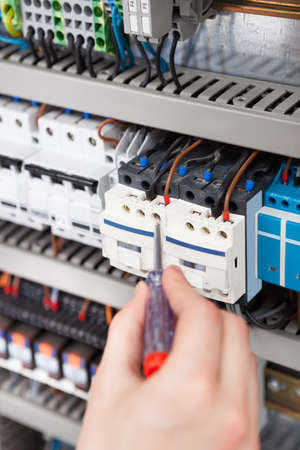 fusebox: Cropped image of male electrician examining fusebox with screwdriver