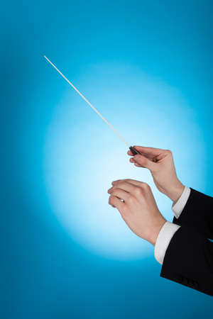 conductors: Cropped image of musician holding baton against blue background