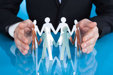 Midsection of businessmans hands protecting team of paper people on desk against blue background photo