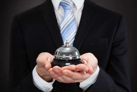 Midsection of businessman holding service bell against black background Stock Photo