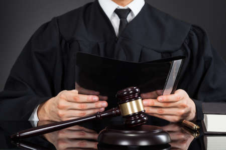 Midsection of male judge holding file with mallet on desk against black background