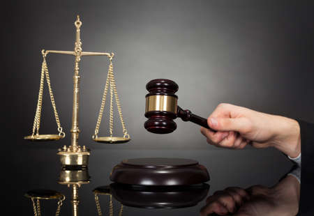 criminal lawyer: Cropped image of male judge with gravel and weight scale at desk against black background