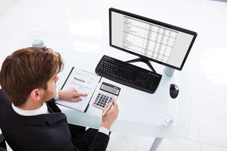 High angle view of businessman calculating expenses at desk in office