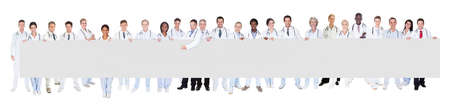 Portrait of multiethnic doctors holding blank banner against white background photo