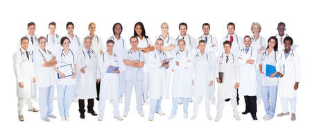 Panoramic shot of confident doctors standing against white background